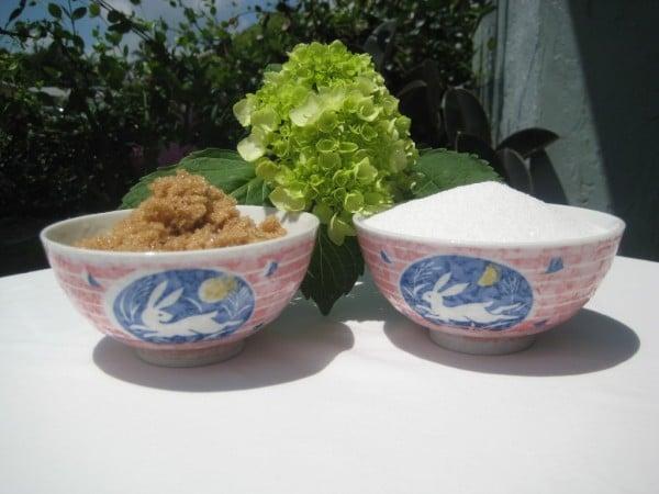 A bowl of white sugar and a bowl of brown sugar