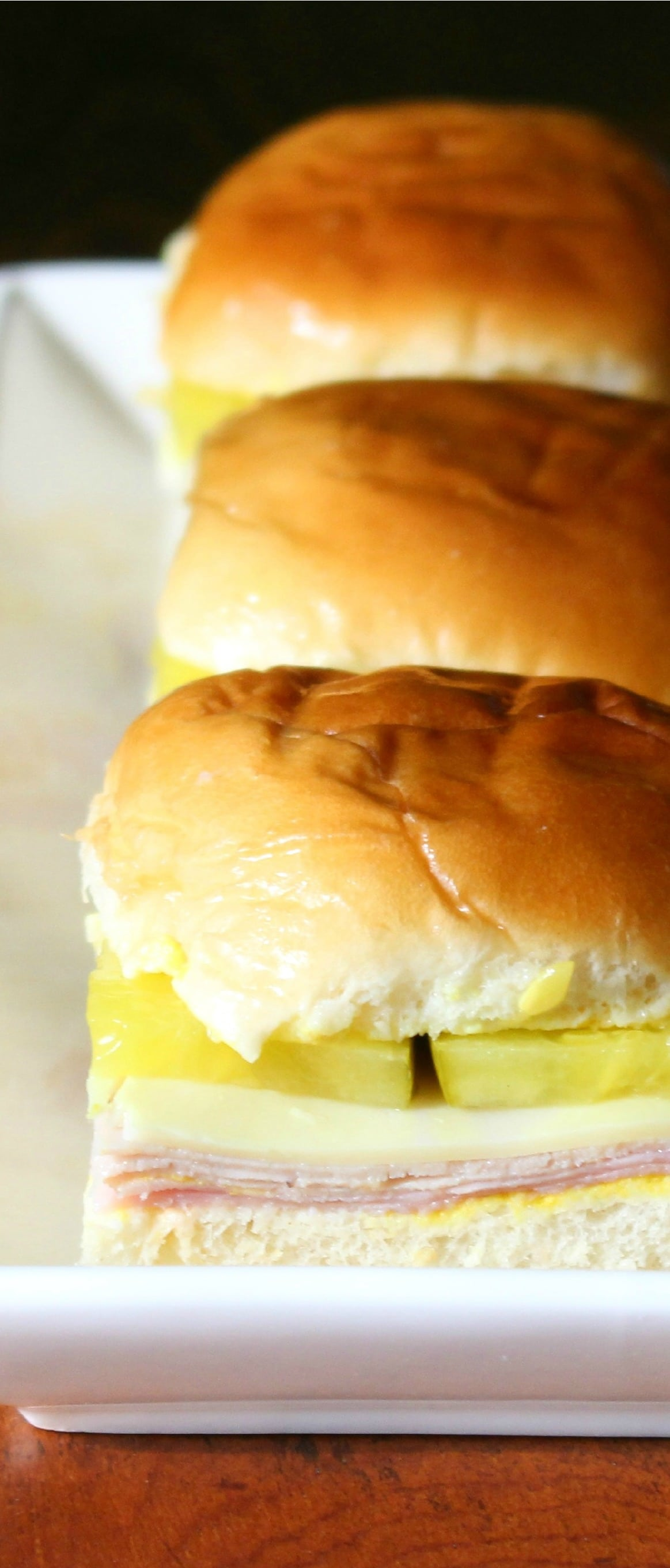 Easy Cuban sandwich sliders made with ham, pork, cheese, mustard, and pickles, on soft dinner rolls.  Bake them for dinner or for a party!