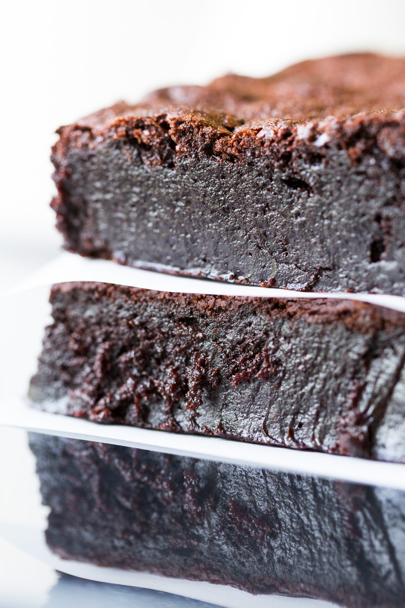 Dark chocolate flourless brownies in a stack with parchment paper