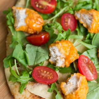 Buffalo Chicken Sandwich on Flatbread with Hummus, Tomatoes, and Arugula