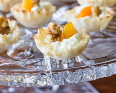 Elegant mini phyllo cups are filled with creamy goat cheese, sweet apricots, and toasted walnuts to make these goat cheese appetizer bites.