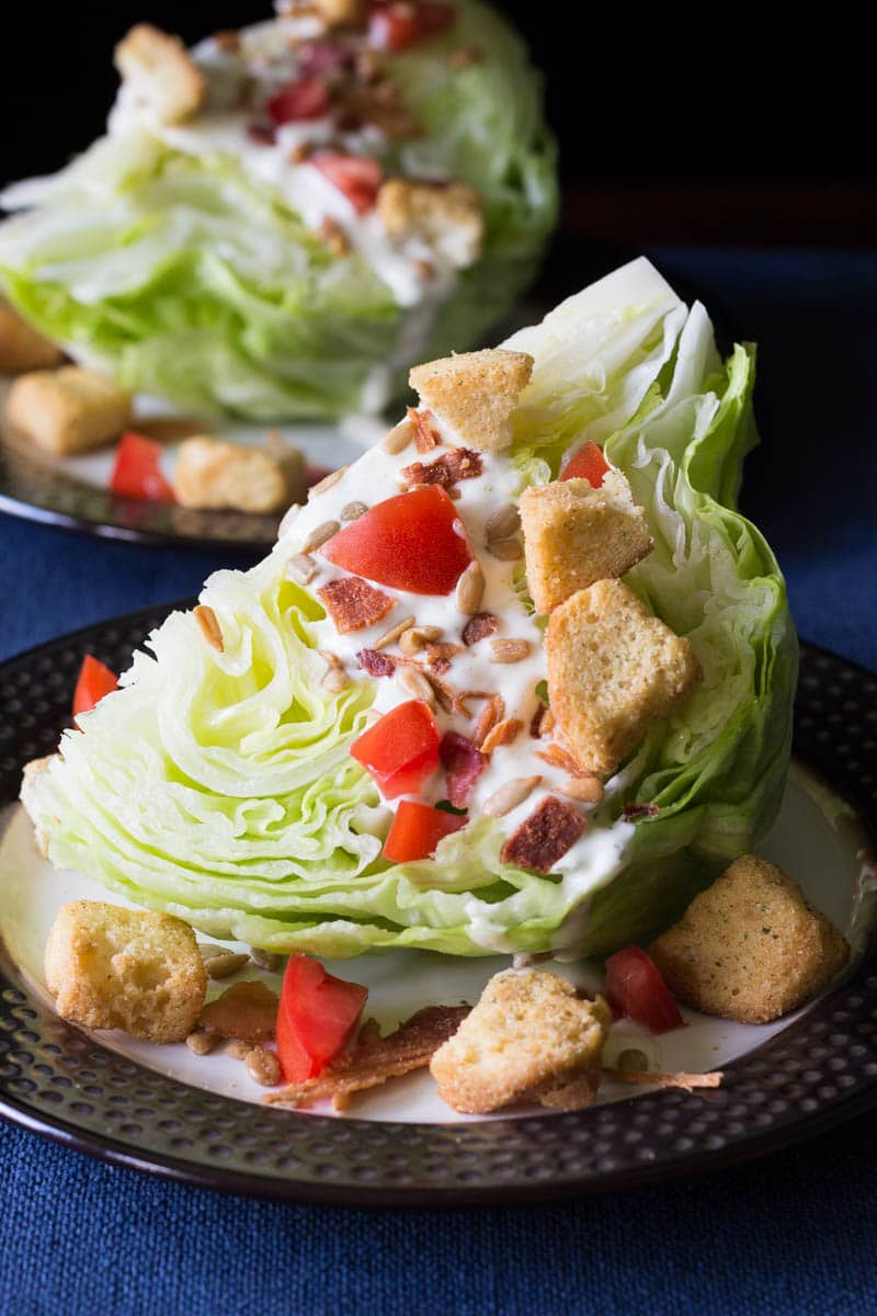 This classic wedge salad recipe is made with crisp iceberg lettuce, crumbly bacon, creamy dressing, and more.