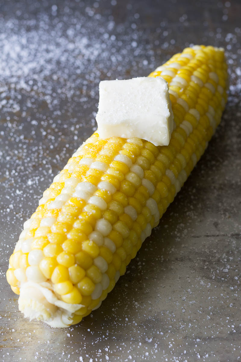 One ear of boiled corn on the cob with butter and sea salt on top