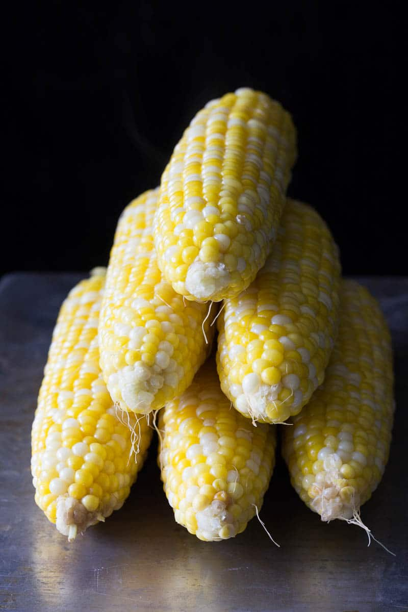 Stack of corn on the cob ears sprinkled with sea salt to show how to boil corn on the cob