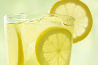 Clear glass of Chick-fil-A lemonade with round lemon slices and ice cubes