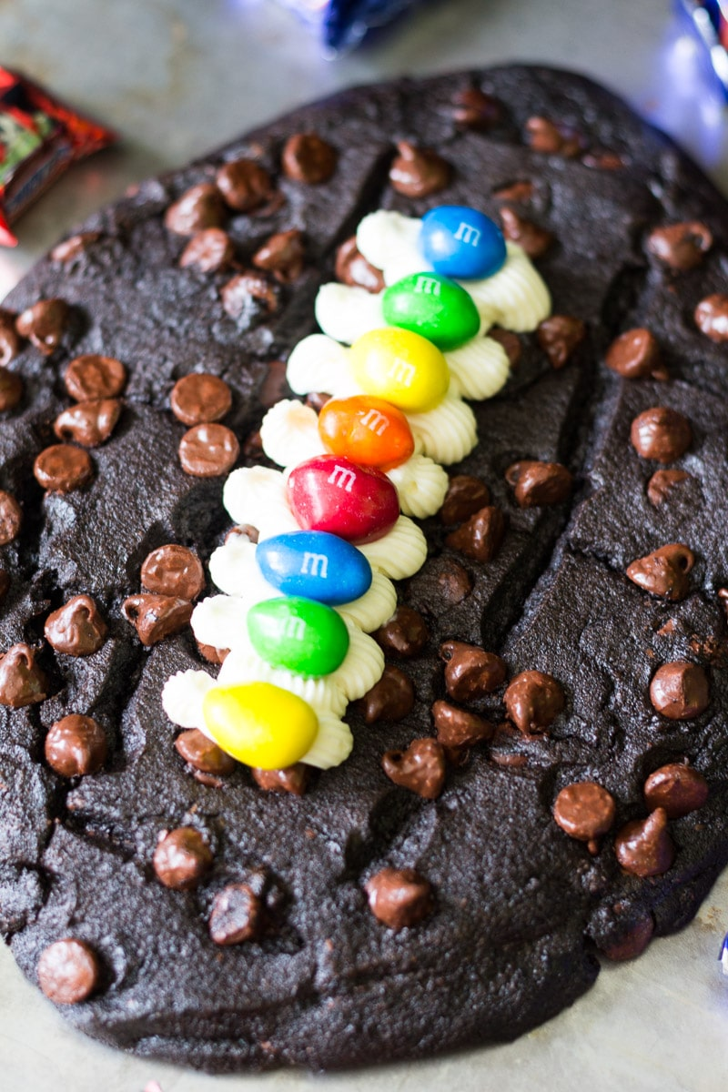 Made with chocolate chocolate chip cookie dough, vanilla frosting, and M&M's, this fun football cookie cake is very easy to make and perfect for parties.