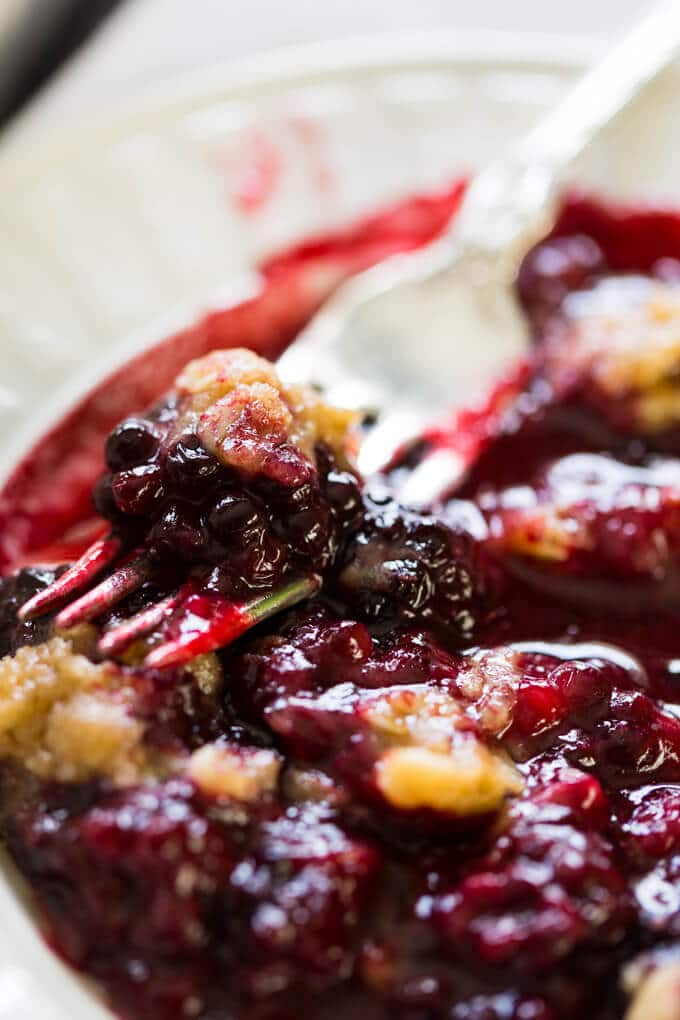 Blackberry crumble on a white plate with a silver fork