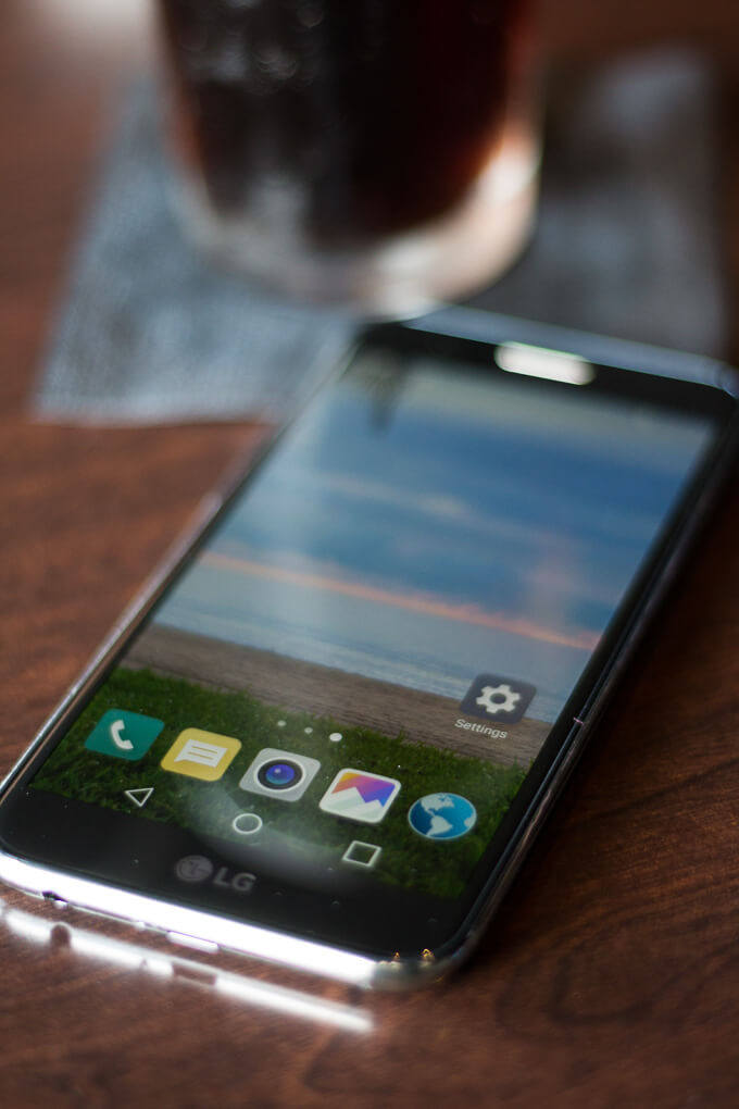 Smartphone to research where should i eat shown with glass of soda on table