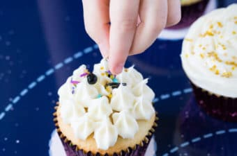 Hand of a child dropping sprinkles on a vanilla cupcake