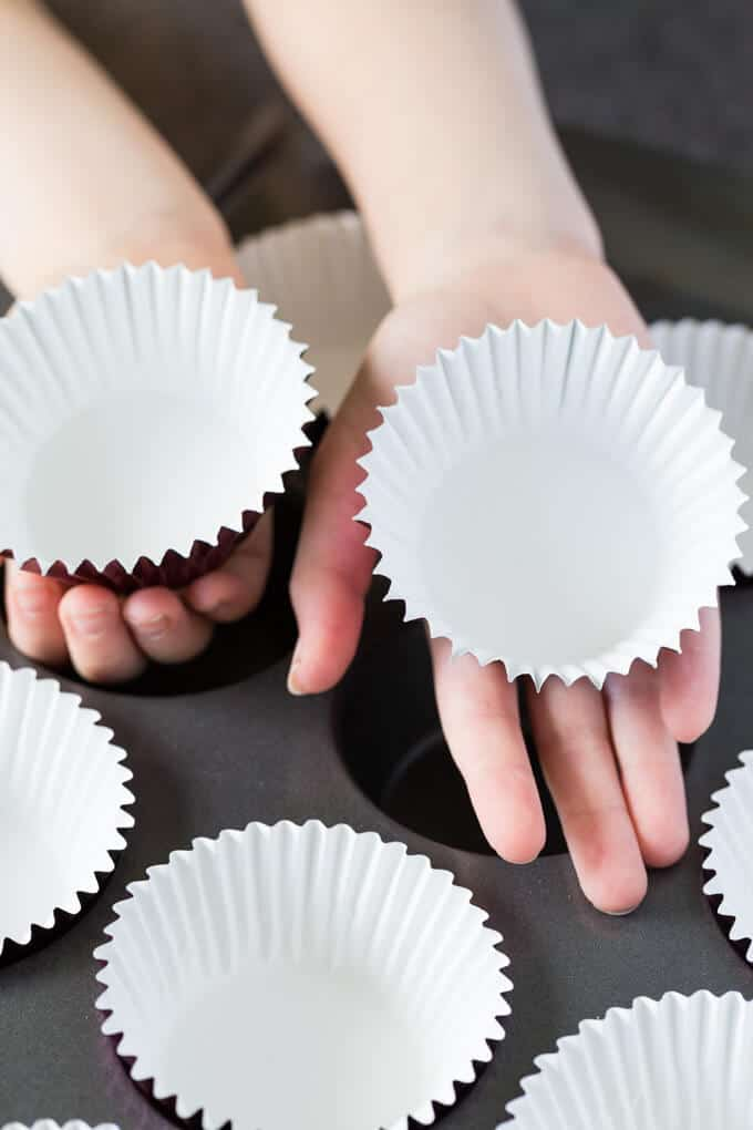Baking with kids - Children's hands holding cupcake liners