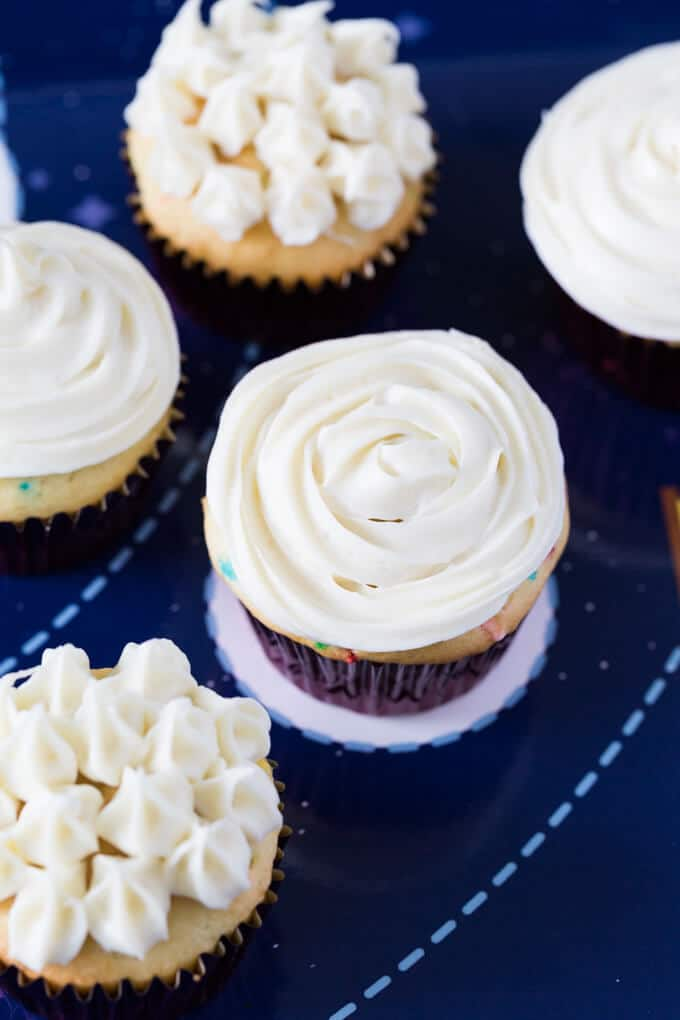 Five vanilla cupcakes with white frosting in different styles