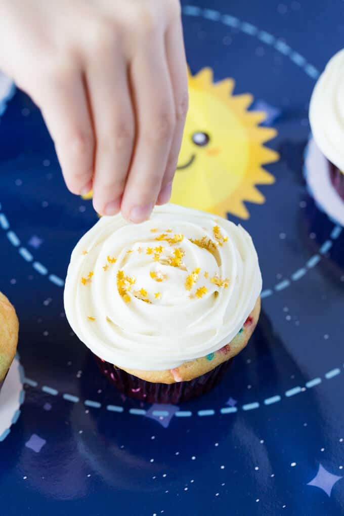 Child's hand sprinkling gold stars on a cupcake