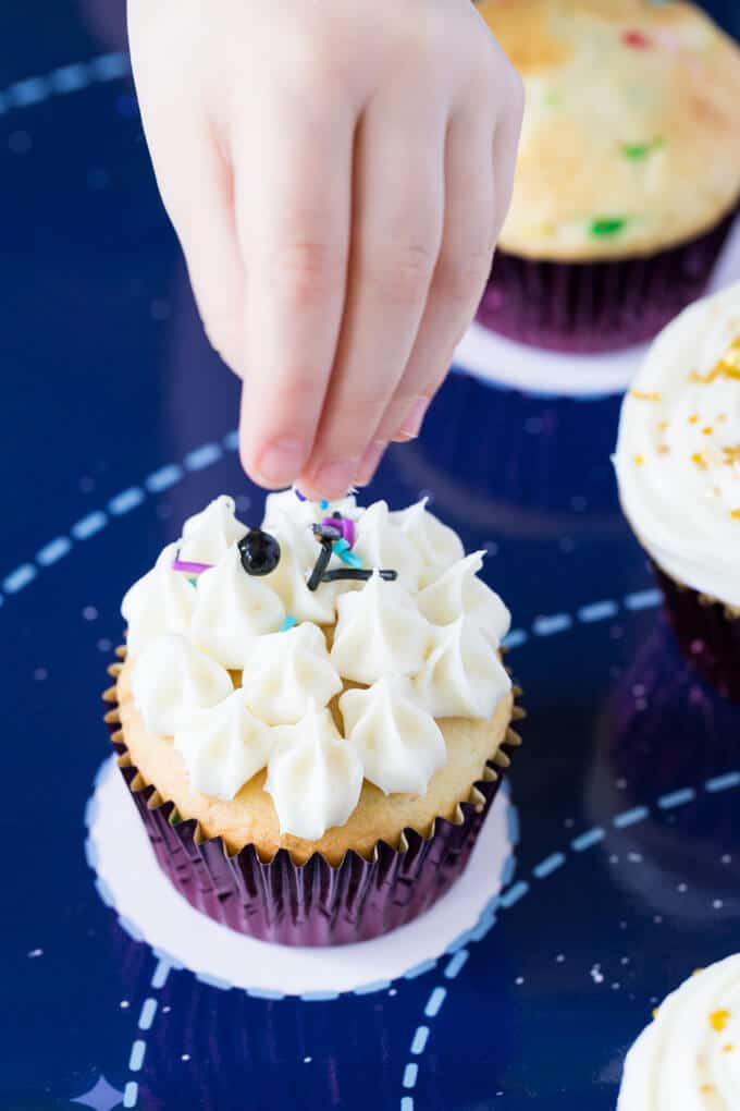 Little girl's hand sprinkling decorations on a cupcake with frosting
