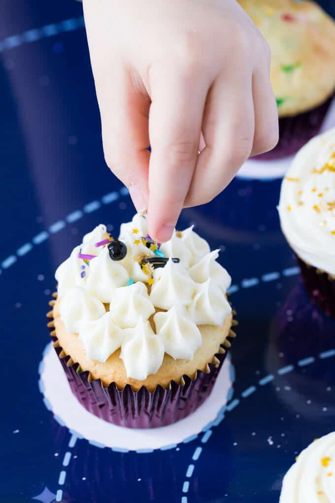 Fingers of a child dropping sprinkles on a cupcake