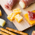 Closeup of kid friendly charcuterie board with meat, cheese, pretzels, and jam