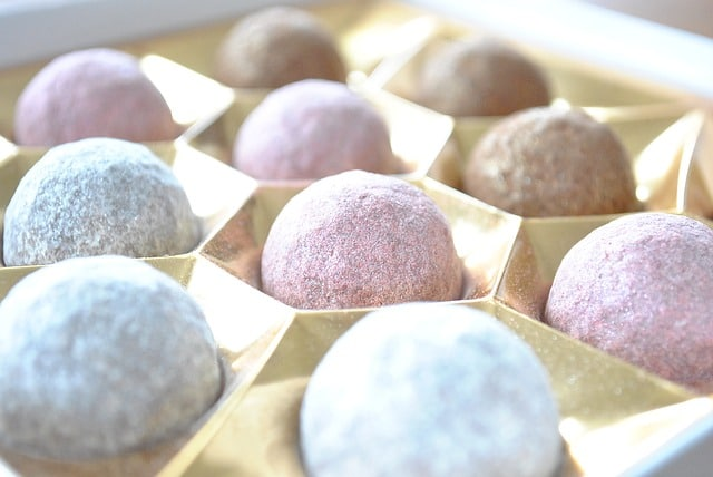 Pastel colored chocolate truffles in gold box