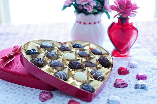 Red heart chocolate box with candy and flowers