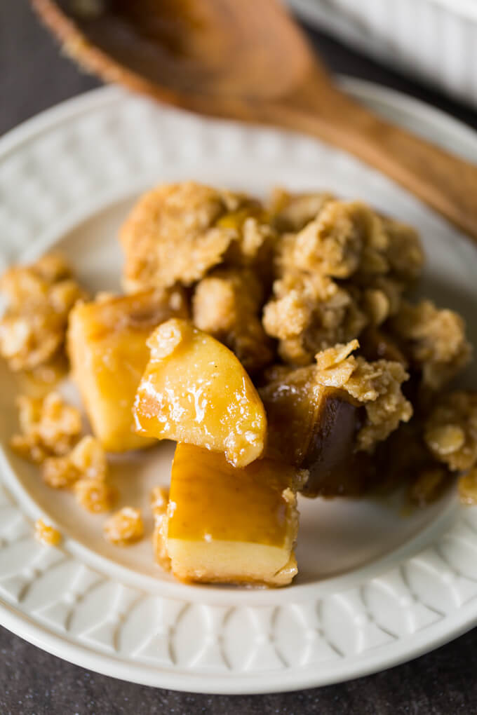 Gluten free apple crisp on a white plate with a wooden serving spoon