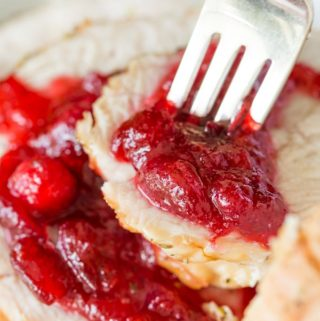 Fork in a stack of turkey breast slices with homemade cranberry sauce