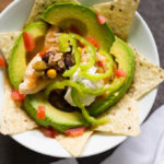 Toppings of avocado and sour cream and peppers on a chicken taco bowl in a white bowl