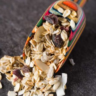 Muesli in a wooden scoop with rainbow colors on a slate background