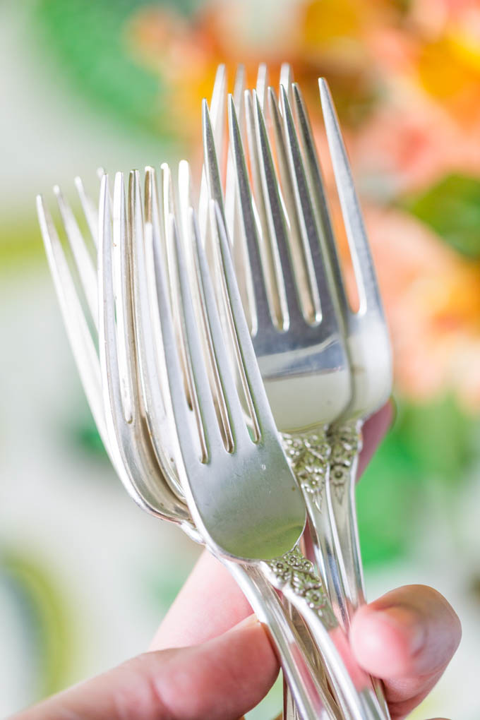 Silver flatware being held near alstroemerias