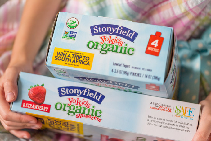 Boxes of Stonyfield YoKids organic yogurt on a girl's lap