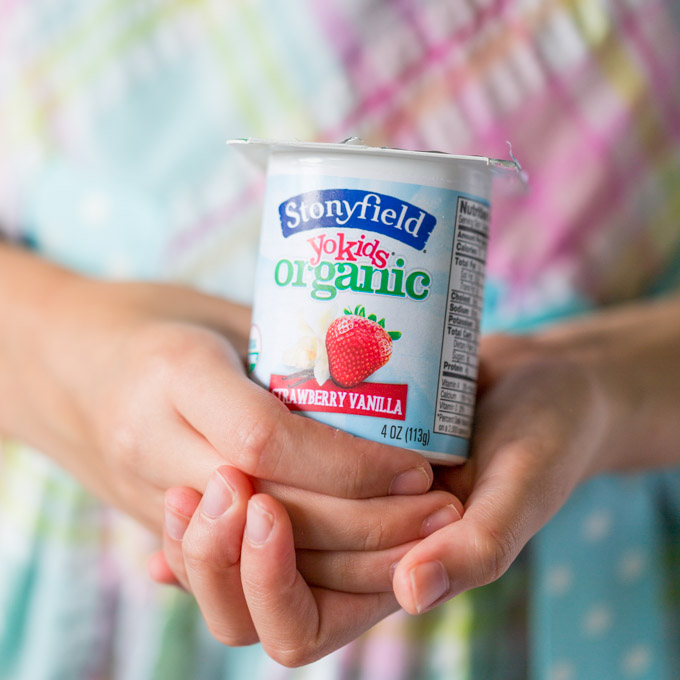 A girl's hands holding a yogurt cup