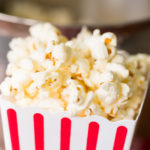 Closeup of popcorn in a red and white striped popcorn bucket