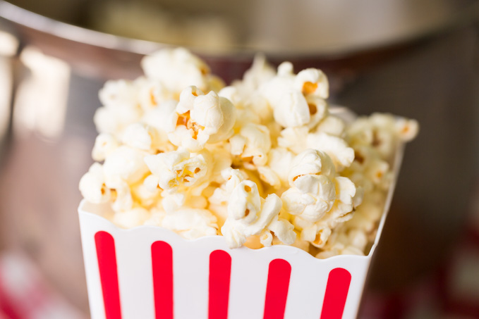 Closeup of movie theater popcorn in a red and white striped popcorn bucket
