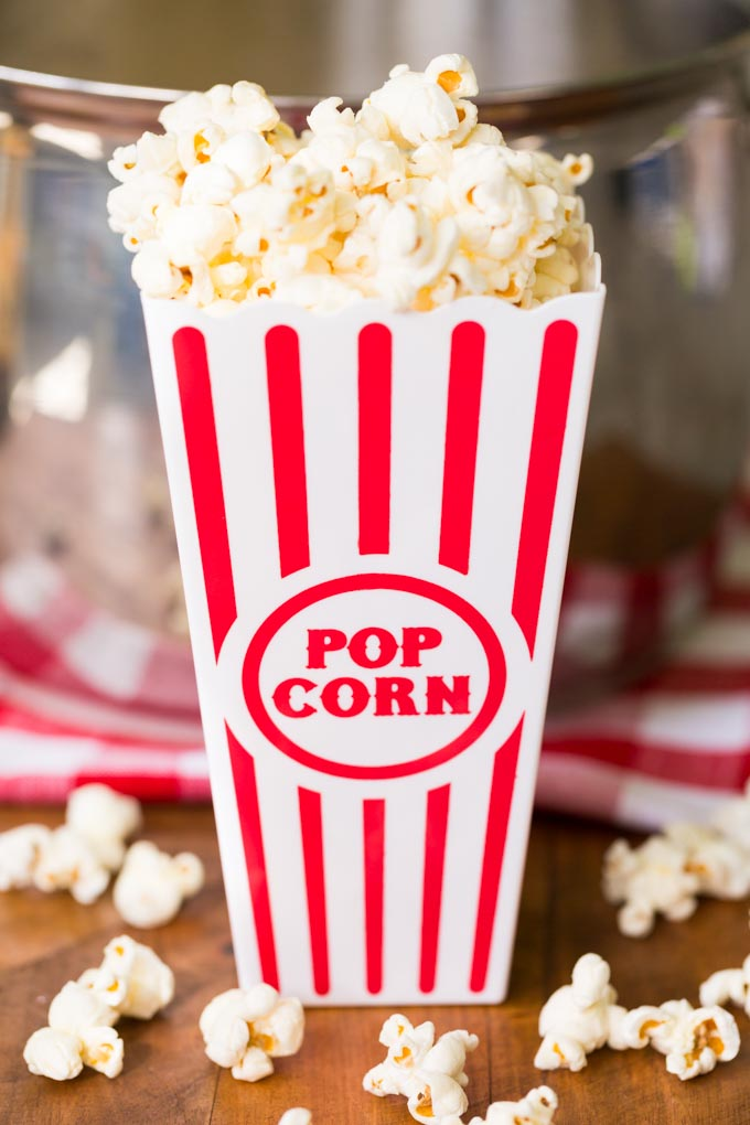 Movie theater popcorn in a red striped popcorn bucket