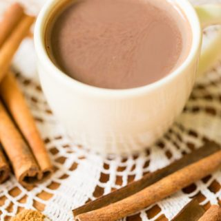 Off white cup of hot cocoa with Ceylon cinnamon and cinnamon sticks on lace