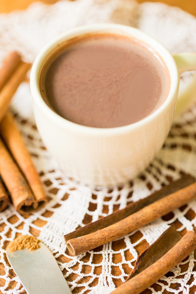 Off white cup of cinnamon hot cocoa with Ceylon cinnamon and cinnamon sticks on lace
