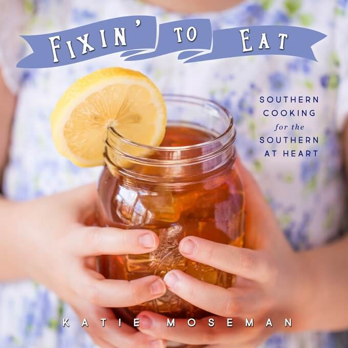 Child's hands holding mason jar of sweet tea with lemon, shown on the cover of Southern cookbook Fixin' to Eat