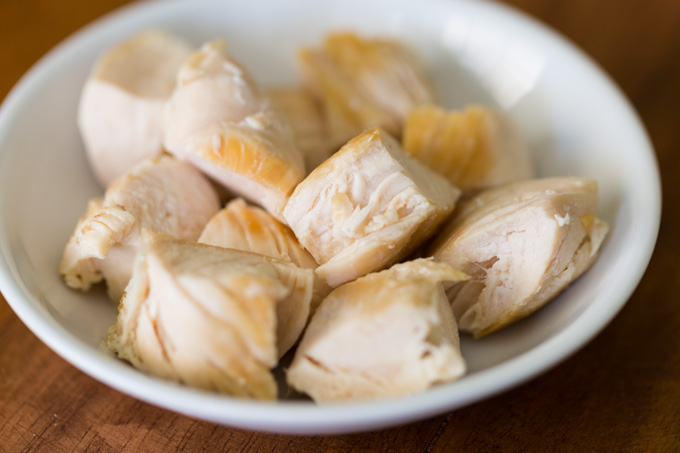 Cut up cooked chicken in a small white plate