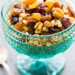 Granola with fruit and nuts in a teal glass footed bowl with a silver spoon