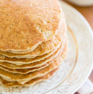 Sorghum pancakes on a white and gold plate on a plaid napkin