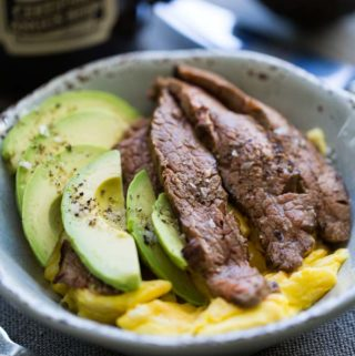 Steak and egg breakfast bowl with fork, mug, and half avocado