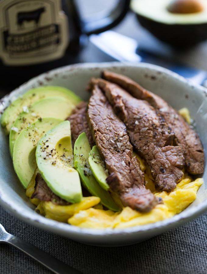 Steak and egg breakfast bowl with fork, mug, and half avocado