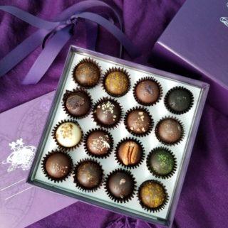 A purple box of gluten free Vosges Chocolate on a purple background