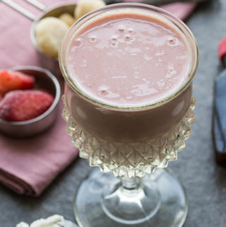 PBJ smoothie in a glass with smoothie ingredients: vanilla frozen yogurt, strawberries, bananas
