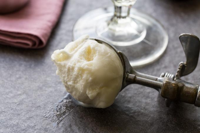 Scoop of vanilla frozen yogurt next to a glass of PBJ smoothie