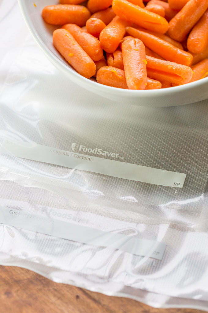 Empty sous vide bags next to carrots in a white bowl