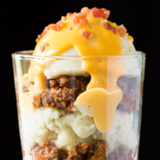 Parfait of mashed potatoes, chili, cheese sauce, and bacon in a glass