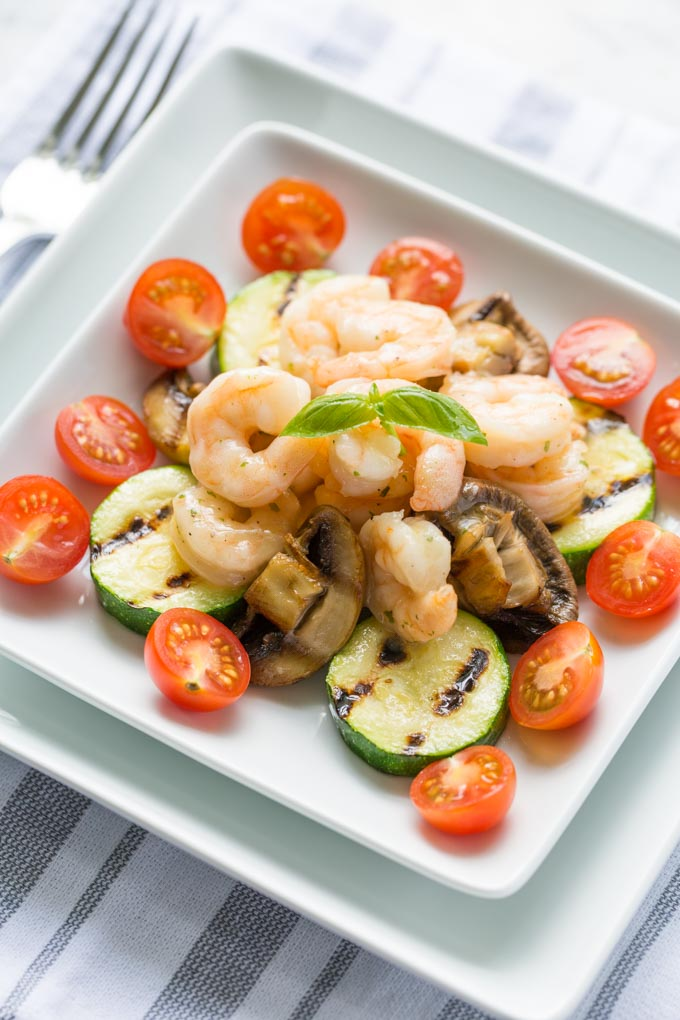 Italian shrimp and vegetables on a white square plate