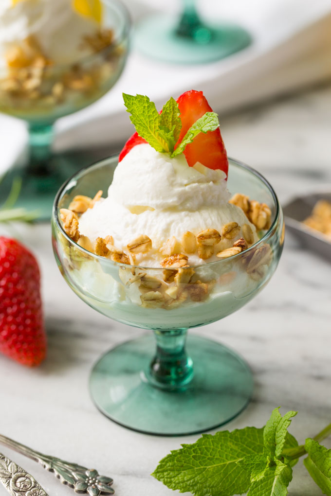 Greek yogurt in a glass with strawberry slice, fresh mint, honey, and granola