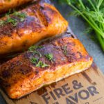 Cedar plank oven salmon on a plank with fresh dill garnish