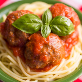 Gluten free meatballs with tomato sauce over gluten free spaghetti in a green bowl