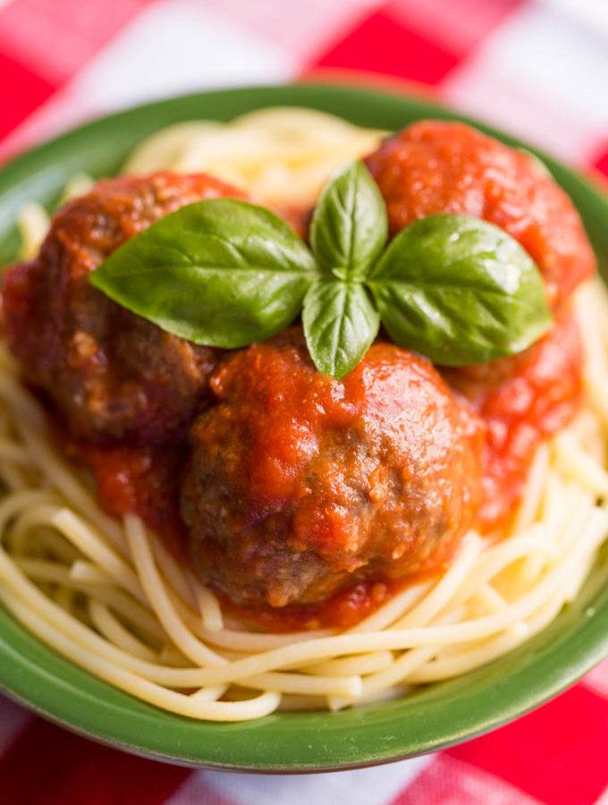 Gluten free meatballs with tomato sauce over gluten free spaghetti in a green bowl