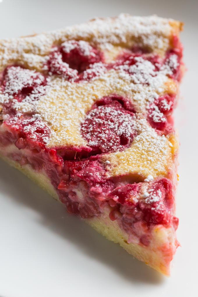 Slice of raspberry clafoutis topped with powdered sugar